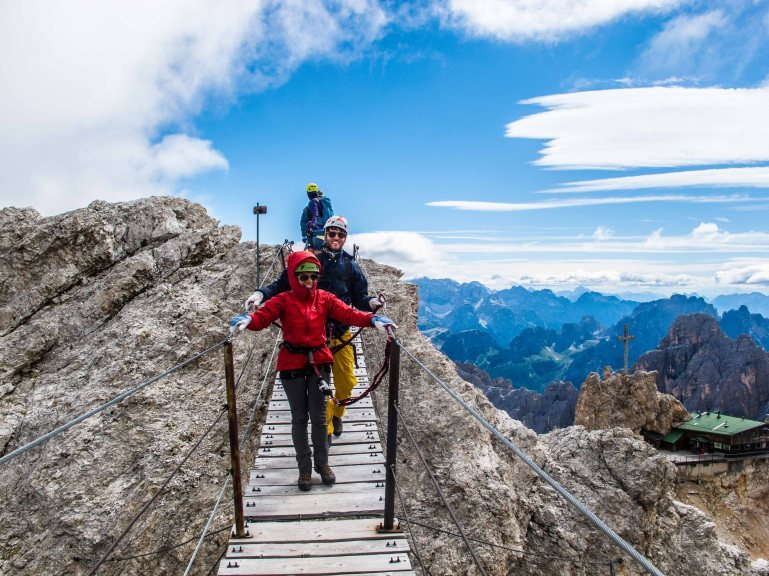 crossing the Suspended bridge on ferrata Ivano Dibona Cortina mountain guide