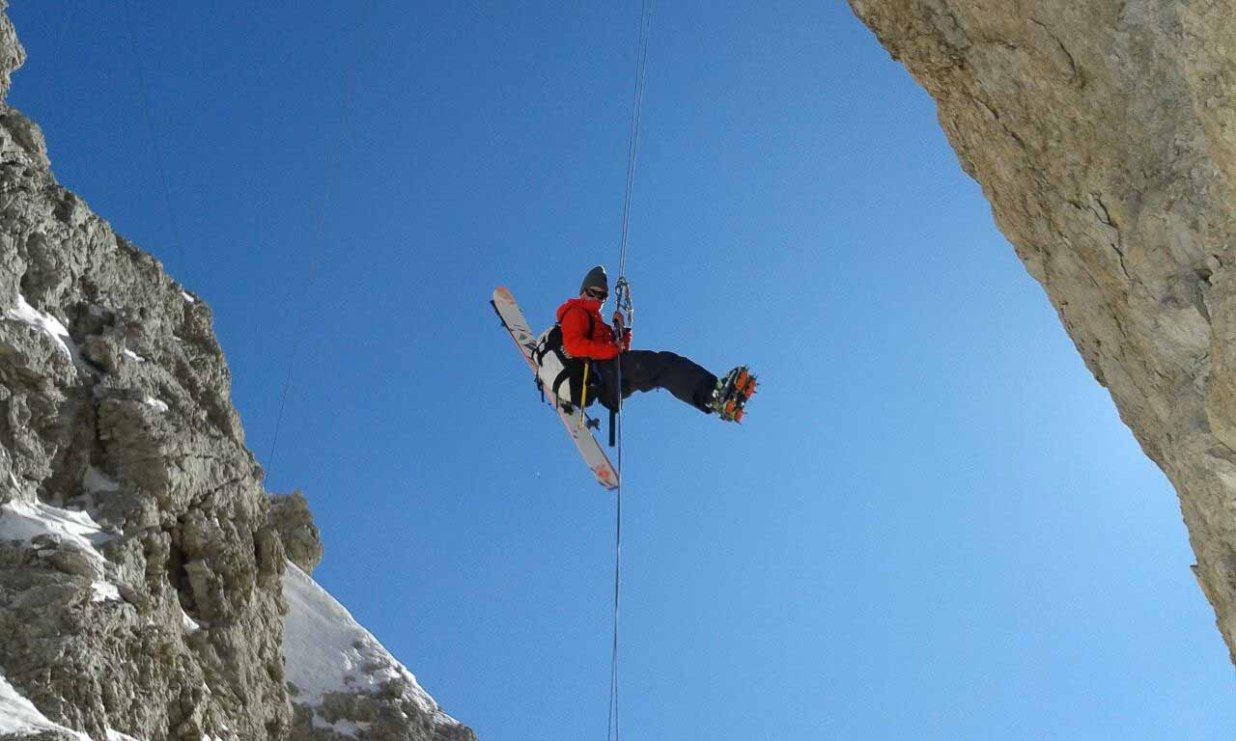 Rappelling down from suspended bridge of ferrata Ivano Dibona in Cristallo.