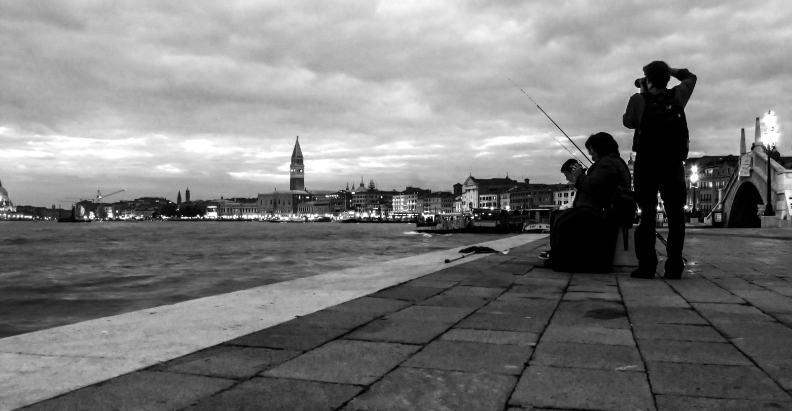 People fishing in Venice, San Marco on the background.