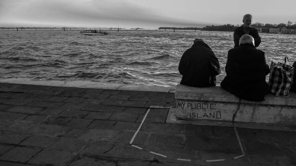 Venice, people sitting close to the lagoon.
