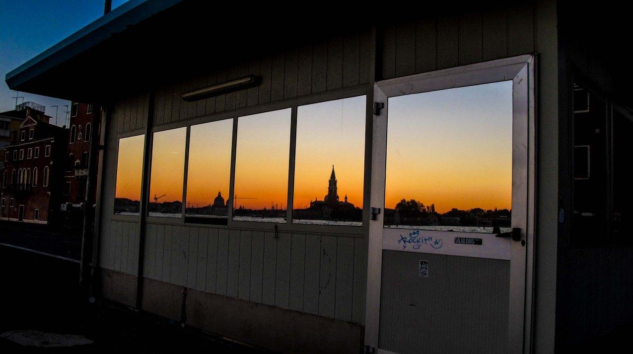 Scorcio di Venezia al tramonto riflesso sul una vetrata.