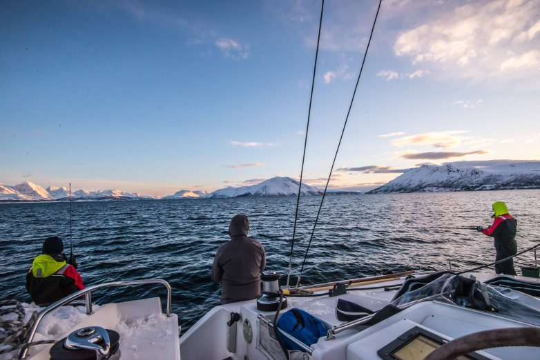 Fishing in the Fjord with snowy mountains in the background.