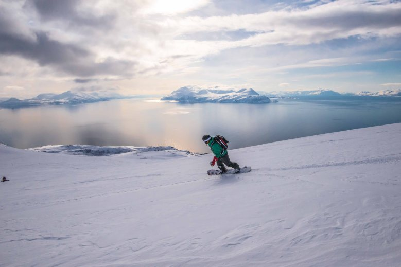 Snowboarding straight to the sea from the summit of Trolltinden in Arnøya.
