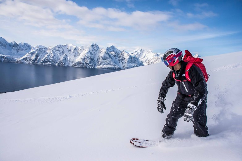 Ride with a view. Snowboard powder freeriding with an amazing view on Lyngen mountains.