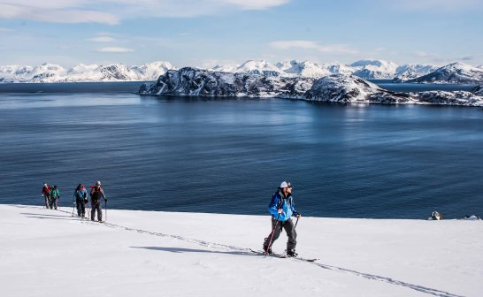 A group skitouring north of Lyngen Alps, amazing contrast with the Norwegian sea in the back