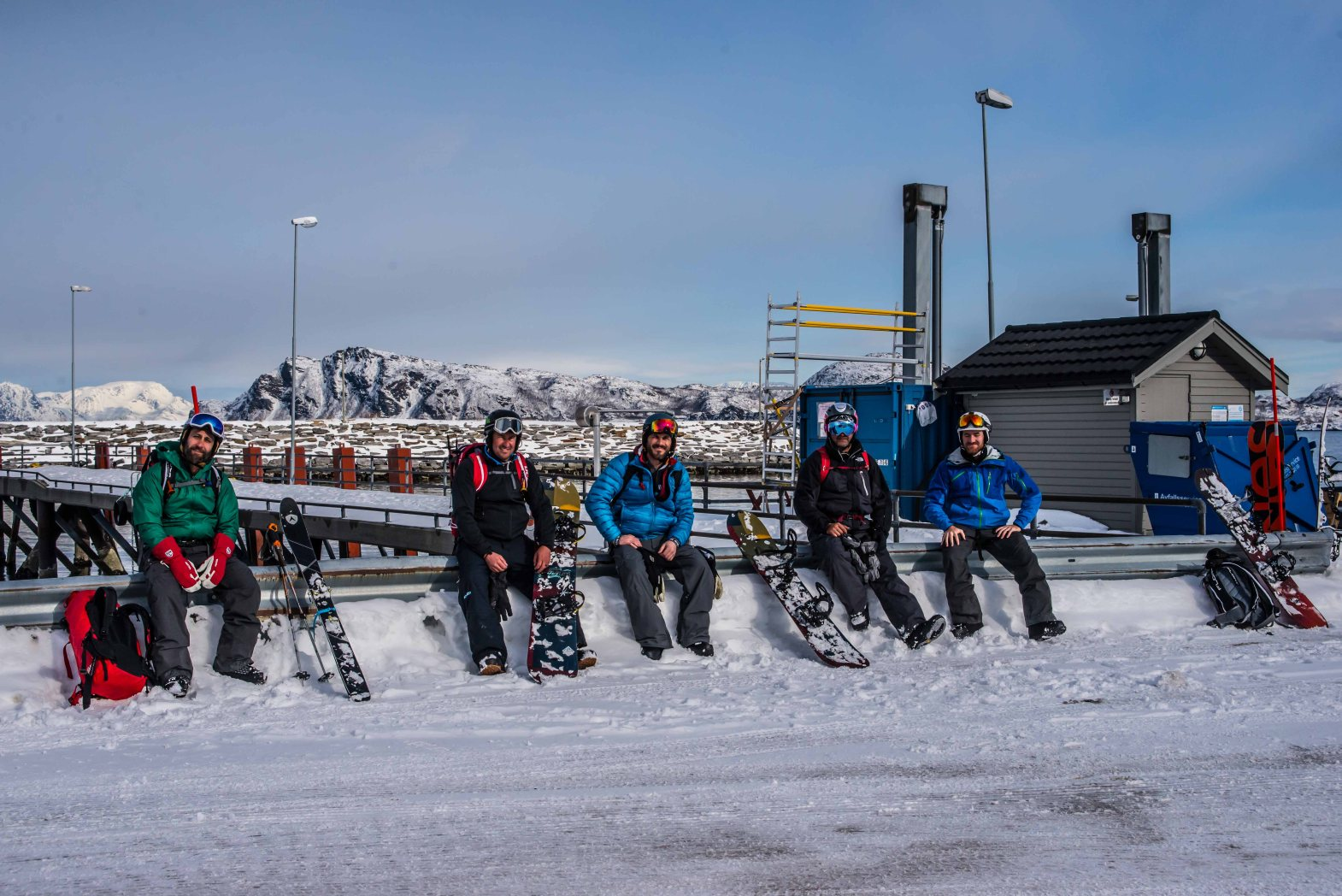 Splitboarders sitting on guard rail at the dock after a good day of freeride in Lyngen.